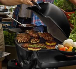 A Black Weber Q1200 with a variety of meats grilling.